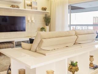 b057c1fea3230 O living conta com um confortável sofá retrátil que acomoda a família na  hora de assistir TV. Um aparador em laca branca envolve o sofá, ...